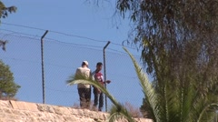 Turkish settlers look into Republic of Cyprus behind north Nicosia fence Stock Footage