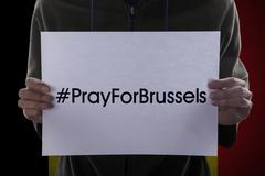 Hands showing text to pray for Brussels - stock photo