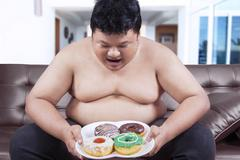 Stock Photo of Hungry overweight man holding donuts