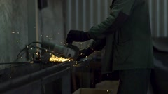 a man cuts metal sparks fly - stock footage