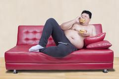 Obese man eats burger while leaning on sofa - stock photo