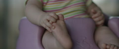 Slow Motion Baby Sitting in Baby Chair Playing with Feet Stock Footage