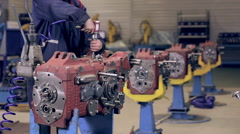 Worker tight nuts on motor, engine by automatic screwdriver Stock Footage
