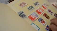 Someone Leafing Album Lists on Which Enshrined Wide Variety of Stamps Stock Footage