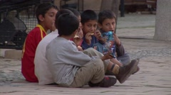 Young Turkish Cypriot children eat junk food snacks in town square Stock Footage