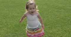 Slow Motion Toddler Girl Running, Jumping, and Smiling in the Grass Stock Footage