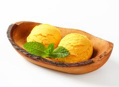 Two scoops of yellow ice-cream in olive wood bowl - stock photo