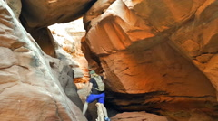 Unidentifiable female hiker in desert slot canyon - stock footage