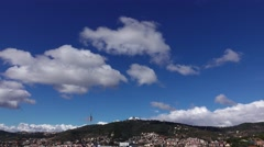 Light cumulus cloud at deep blue sky over Tibidabo mountain, time lapse shot. Stock Footage
