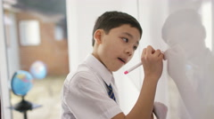 4K Happy school boy in class listening to teacher & writing on whiteboard - stock footage