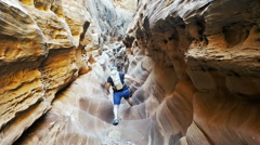 Unidentifiable female hiker in desert slot canyon Stock Footage