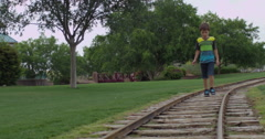 Slow Motion Brown Haired Boy Walking on a Train Track Stock Footage