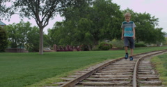 Slow Motion Blonde Haired Boy Walks on a Train Track Stock Footage