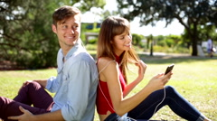 Pretty female with male enjoying music in the park Stock Footage