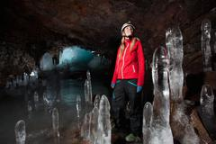 Hiker with stalactites in glacial cave - stock photo