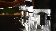 Barista pouring hot water in a glass. Stock Footage