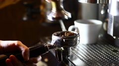 Stock Video Footage of Detail of hand pressing coffee, an espresso making machine and a cup.