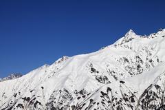 Snowy mountain peaks and blue clear sky Stock Photos