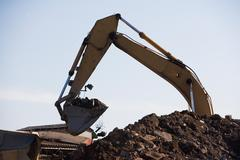 Earth mover and pile of rubble Stock Photos