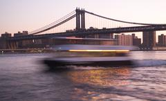 Stock Photo of Boat in motion on East River by Manhattan Bridge, New York City, USA