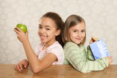 One girl with an apple, one girl with a packet of crisps Stock Photos