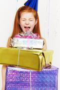 Screaming girl with stack of birthday gifts Stock Photos