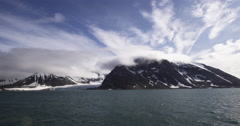 Arctic mountains in sun and clouds next to ocean from ship Stock Footage