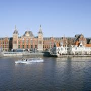 canal cruise boat in front of amsterdam central railway station - stock photo