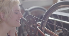 Young woman oils bike chain in urban loft setting 4K Stock Footage