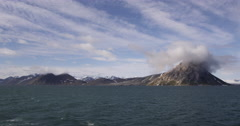 Steaming away from mysterious cloudy mountains on ship - stock footage