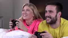 Young couple in pajamas playing video game together, slowmotion, closeup - stock footage