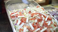 Juicy salad with tomatoes, onions, olives, cucumbers, cheese in a glass case - stock footage