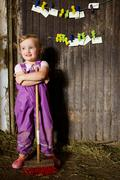 Girl in overalls sweeping in barn Stock Photos