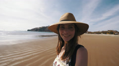 Woman smiles to camera while exploring a beach. 4K Broadcast Quality Stock Footage