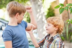 Boy feeling brothers biceps outdoors Stock Photos