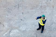 Worker using walkie-talkie on dry dock Kuvituskuvat
