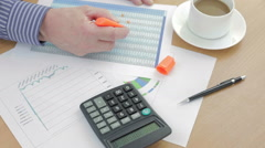 Account at his desk using a highlighter on a spreadsheet - stock footage