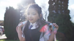 4K Portrait of smiling little girl with backpack, outdoors in school playground Arkistovideo