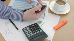 Accountant using his smart phone while working at his desk - stock footage
