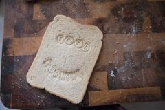 """Good morning"" stamped into bread Stock Photos"