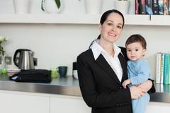 Businesswoman holding baby son Stock Photos