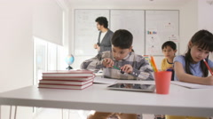 4K Portrait of happy little boy working at his desk in school classroom Stock Footage