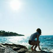 Young woman crouching by the sea Stock Photos
