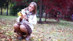 Beautiful elegant woman collects leaves in a park in autumn. 1920x1080 Stock Footage