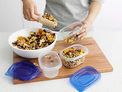 Woman scooping granola into tupperware - stock photo