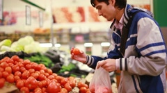 Man buys tomato vegetable in grocery shop. 1920x1080 Stock Footage