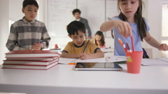 4K Portrait of happy little boy working at his desk in school classroom Stock Footage
