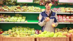 Man has a fun while takes an apple in a grocery store. 1920x1080 Stock Footage