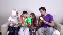 Family launches colorful paper airplanes in the room, slowmotion Stock Footage