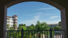 Resort with Blue Skies and Palm Trees Time Lapse Looking Through Window, 4K Stock Footage